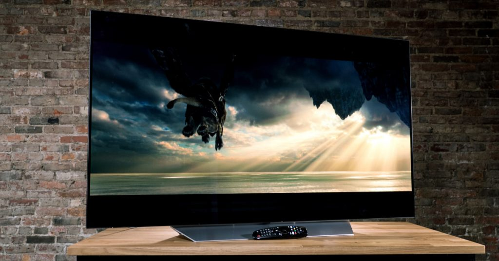 picture of a TV on a desk, with a remote control beneath it and a brick wall behind it