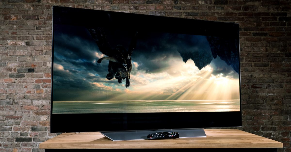 picture of a LG C7 OLED 4K TV on a desk, with a remote control beneath it and a brick wall behind it