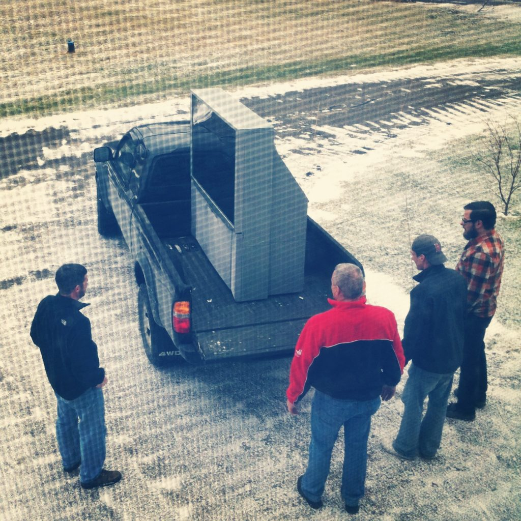 4 men standing around a van which has a huge television set in its trailer